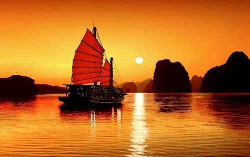 Tourists enjoy the amazing sunset in Halong bay
