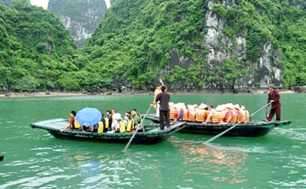 Paradise Cruise's travellers discovering Luon Cave on local canoes