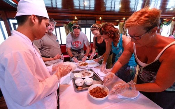 Travellers learning how to cook Vietnamese food in a cooking class on boat