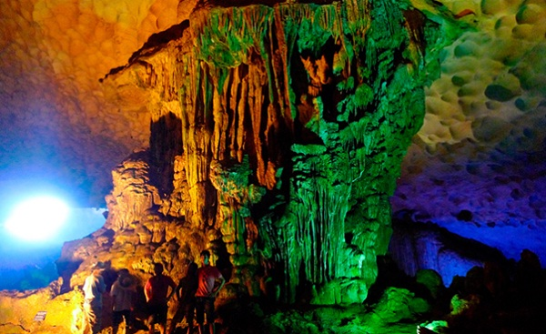 Colorful lights reflected on rock walls in Dau Go Cave