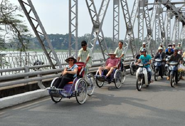 Tourist traveling by Xich Lo on Truong Tien Bridge