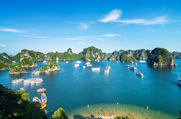 Tour boats and cruise ships passing by limestone islands in Halong Bay